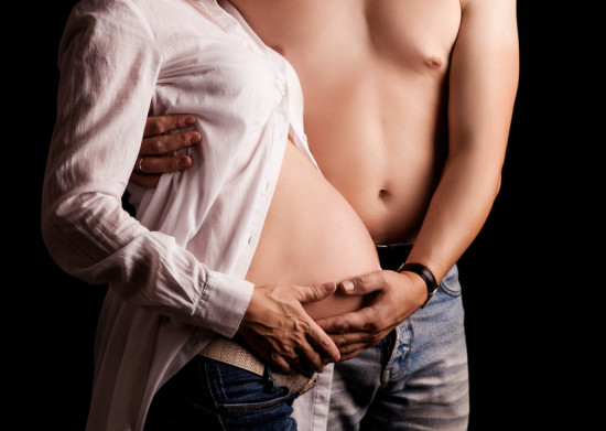 hands and torso of a pregnant woman and her husband, isolated on black studio background